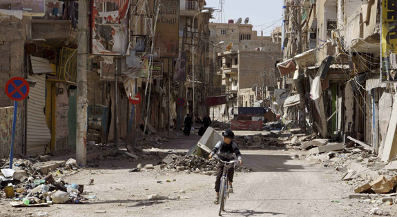 Boy rides his bicycle past damaged buildings in Syria