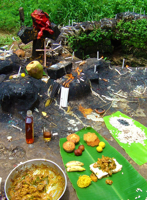 The offering:  Brandy, chicken masala, bananas, ladoos, sliced bread, fried local snacks, jelebis laid out on a banana leaf. I drank the brandy and ate some of the offering. © Mark Ulyseas