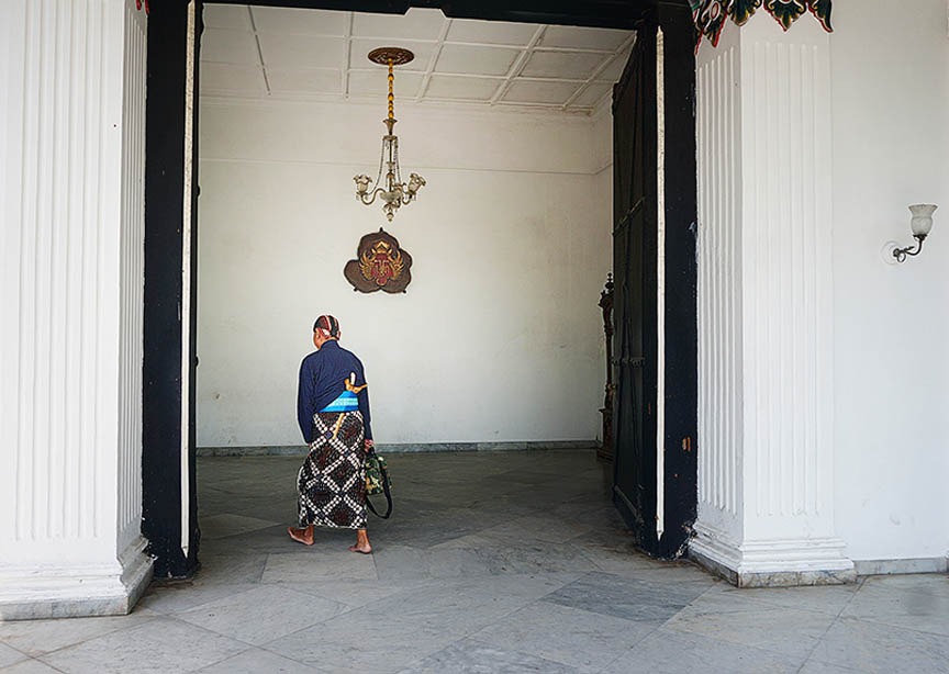 Off to work. This abdi dalem or palace guard hurries into work through the ten feet thick palace walls thus entering another quieter more refined world. © Jill Gocher